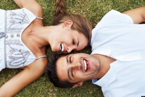 High angle view of happy couple lying together on grass